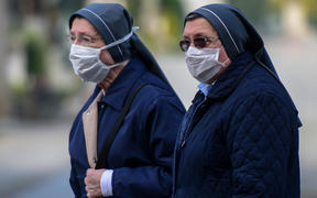 Nuns wearing face masks stand inside the closed Monumental Cemetery of Bergamo, Lombardy during the country's lockdown.