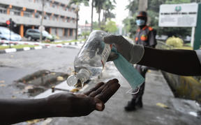 A visitor tries to sanitise hands before being allowed into a state hospital at Yaba in Lagos.