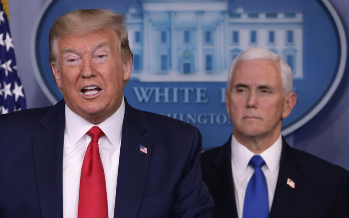 President Donald Trump is flanked by Vice President Mike Pence while speaking during a news briefing on the latest development of the coronavirus outbreak in the US at the White House on 18 March.