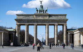 Passers-by stand on Pariser Platz in front of the Brandenburg Gate, 20 March.