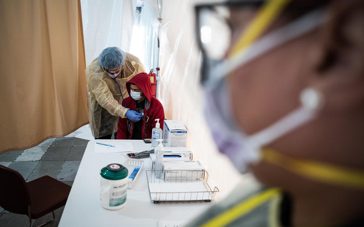 A doctor examines a patient for a COVID-19 test inside a testing tent in New York.