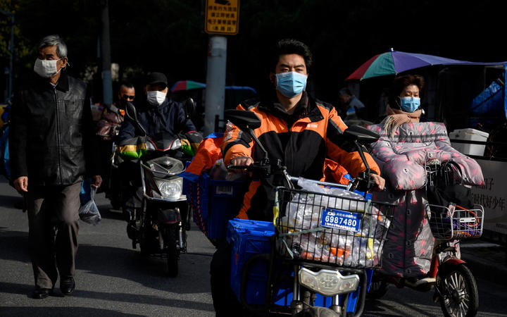 Motorists wearing face masks, amid concerns over the spread of the COVID-19 novel coronavirus, commute along a street in Shanghai on March 23, 2020.