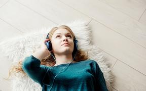 Beautiful blond woman listening to music through headphones. Lying on a wooden floor.