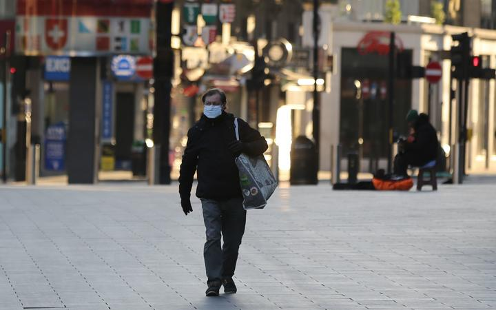 A man wears a medical mask as a precaution against coronavirus at deserted Leicester Square in London, United Kingdom on March 23, 2020.