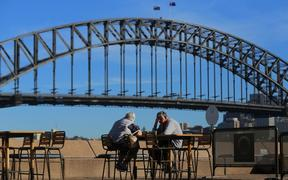 SYDNEY, AUSTRALIA - MARCH 19: An elderly couple sit at a table in front of the Sydney Harbour Bridge, following an outbreak of coronavirus (COVID-19), in Sydney, Australia.