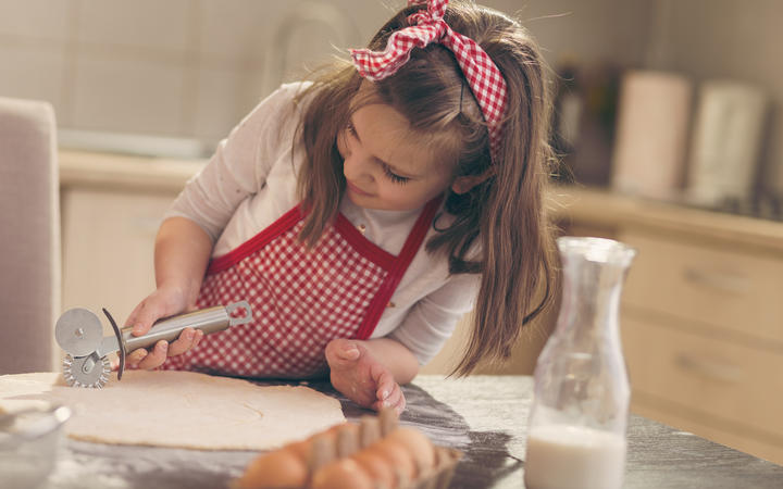 Little girl with apron in kitchen cutting dough.