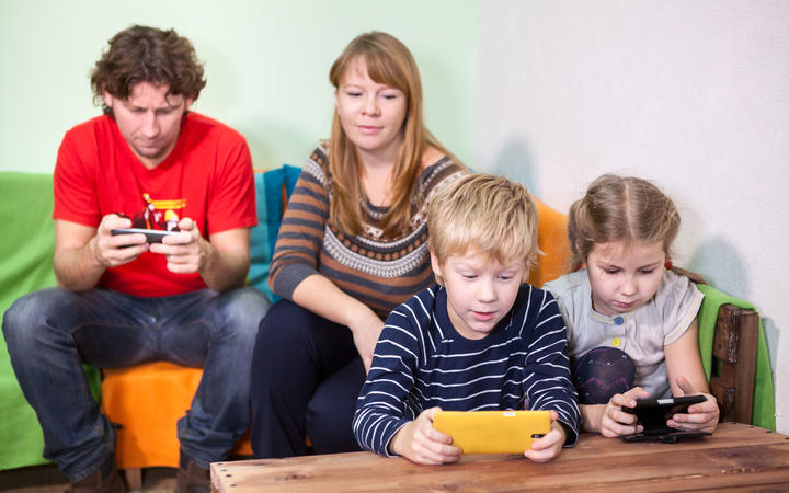 36913913 - children and husband are passionate about games in the phone, mother looking at the kids