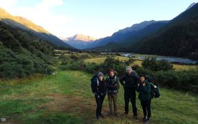 Pauline Dupont and Romain (left) and friends tramping in New Zealand. They emerged from the bush to find the world had turned upside down.