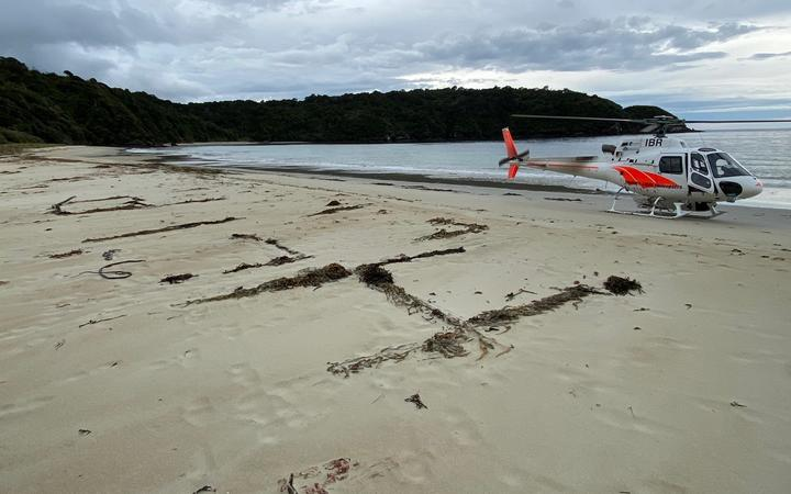 A 'help' sign is written in sand on Chew Tobacco Bay in Stewart Island beside a rescue helicopter.