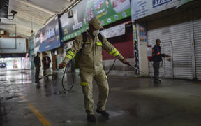 "Cleaning personnel spray disinfectant at the ""Central de Abasto"" wholesale market, the biggest food supply central in Mexico City, on March 24, 2020 to fight against the coronavirus Covid-19 outbreak."