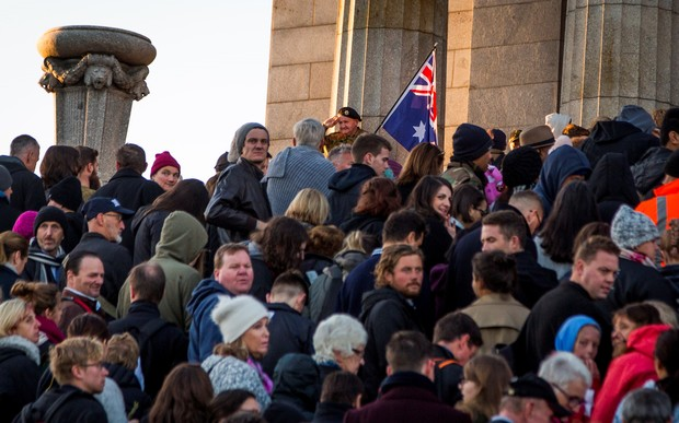 People line up to pay their respects as an elderly man salutes crowd during the Anzac dawn service in Melbourne.