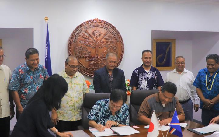 Japan Ambassador Norio Saito and Marshall Islands Foreign Minister Casten Nemra sign two agreements as President David Kabua and his Cabinet look on