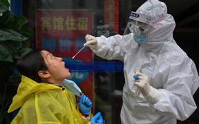 A medical worker takes a swab sample from a person to be tested for the COVID-19 novel coronavirus in Wuhan, China's central Hubei province on March 29, 2020, a day after travel restrictions into the city were eased following the outbreak.