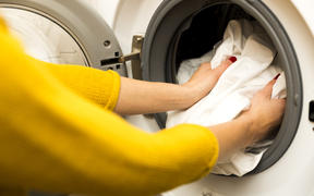 Woman hand loading dirty clothes in washing machine.