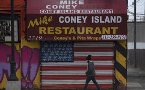 A man passes a closed restaurant near the Eastern Markets in Detroit, Michigan on 24 March 2020.
