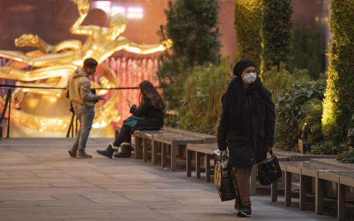 A woman wearing a face mask walks along Rockefeller Center Plaza on Friday, March 2020 in New York, NY.