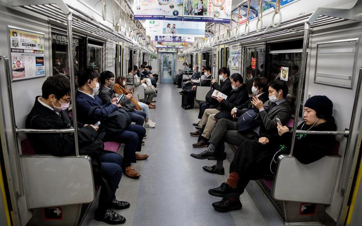 People wearing face masks amid concerns over the spread of the Covid-19 coronavirus, commute on a train in Tokyo on 6 April 2020.