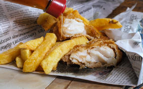 Fish and chips wrapped in newspaper.