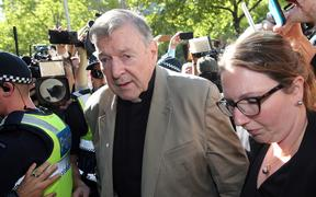 This file photo taken on February 27, 2019 shows Australian Cardinal George Pell (C) making his way to the court in Melbourne. - Cardinal George Pell will walk free from jail after winning a long-running battle to overturn his child sex abuse convictions in Australia's High Court on April 7, 2020.