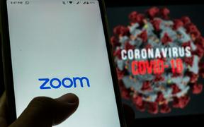 Logo of Zoom, video conferencing application services company is seen with the text of coronavirus COVID-19 in the back of it in Yogyakarta, Indonesia on April 3, 2020. Zoom video conferencing application is used to have a group chat from their separate homes, due to the coronavirus COVID-19.