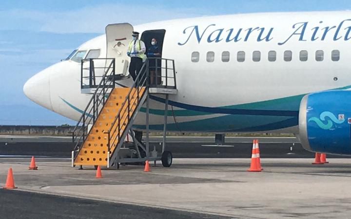 A Nauru Airlines pilot, donned in Covid-19 prevention gear, waits for local officials to collect flight manifest documents. No passengers or crew deplaned from Friday's flight to Majuro, which took about 10 passengers out of Majuro.