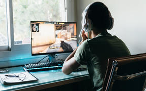 Teenager playing Counter Strike Global Offensive video game on PC. CSGO is an online multiplayer video game developed by Valve