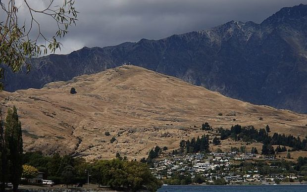 View from Queenstown to  the Remarkable Range showing numerous small wilding pines spreading across Kelvin Heights
