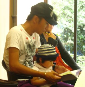 A father and his young daughter attending a Chinese parenting lecture