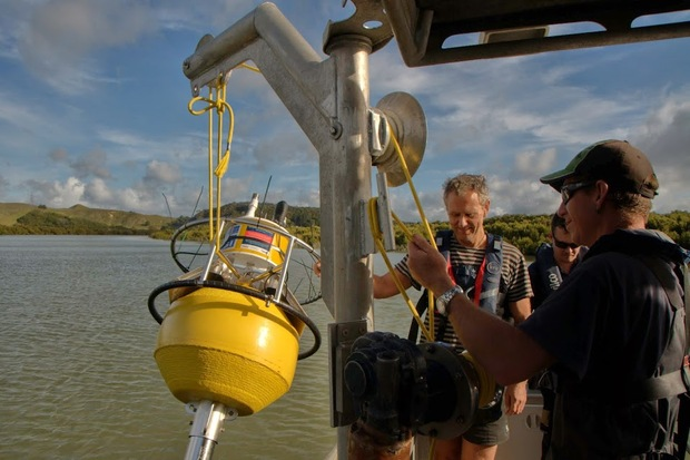 Lowering an estuarine monitoring buoy over the side of a boat