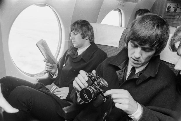 Beatles Ringo Starr and George Harrison on a plane with book and camera by Morrie Hill courtesy ATL