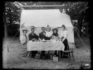 Six unidentified people sitting at a table having a cup of tea