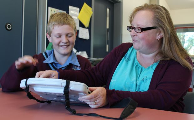 Nathan Carter works on the ipad with his teacher aide Sam Newbigging