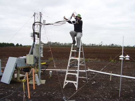 Susanna Rutledge setting up the eddy covariance carbon dioxide measuring system on a tower above bare peat soil