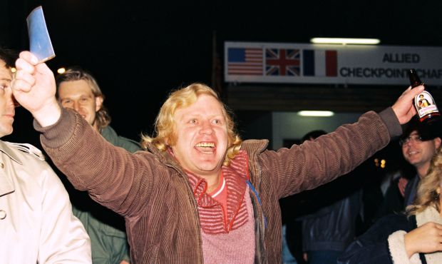 Jubilation at Checkpoint Charlie GDR documents in one hand a West German beer in the other