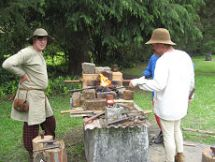Living history medievalists gater around a fire.