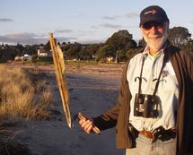 Julian Pettifer at maketu with a piece of container debris from the Rena