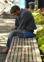 A homeless man sits out the day on a bench in Auckland