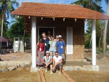 Building October Completed house with volunteer team and grateful owners Mary right and Sheldon left Copyright Iain Pearson small