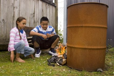 Two youngsters stare at a small fire lit from a bundle of paper