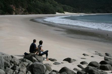 Two tourists sit admiring the pristine beauty of New Chums beach in Coromandel