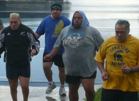 A group of overweight men work out at