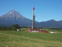 An oil well dominates a green site in front of Mt Taranaki